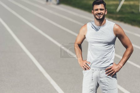smiling young sporty man standing on running track with arms akimbo