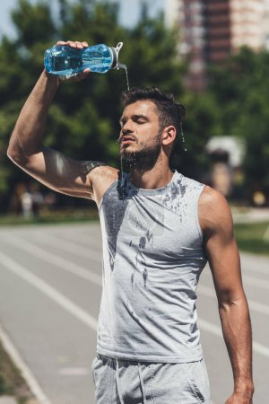athletic young man pouring water on himself after training
