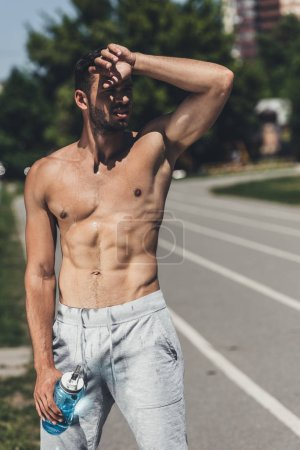 sweat shirtless young man standing on running track after workout and wiping forehead
