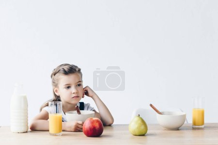 lonely little schoolgirl sitting at table during breakfast and looking away isolated on white