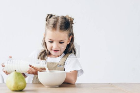 little schoolgirl pouring milk into bowl with breakfast isolated on white