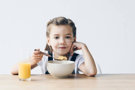 Photo for Smiling little schoolgirl eating healthy breakfast isolated on white - Royalty Free Image