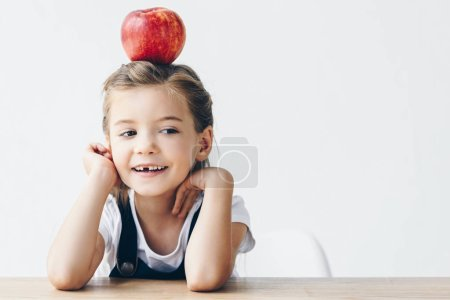 little schoolgirl sitting at table with red apple on head isolated on white