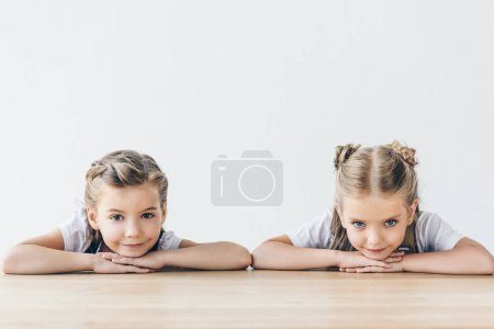 children sitting at table and looking at camera isolated on white