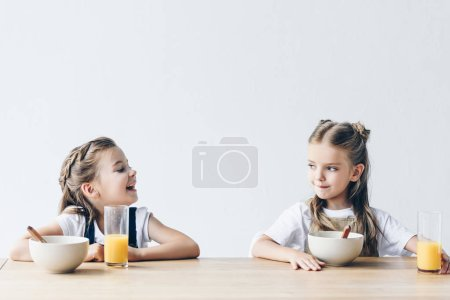 adorable smiling schoolgirls eating cereals with orange juice for breakfast isolated on white