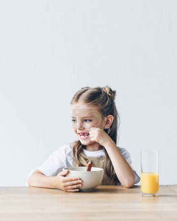 happy little schoolgirl with bowl of breakfast and orange juice isolated on white