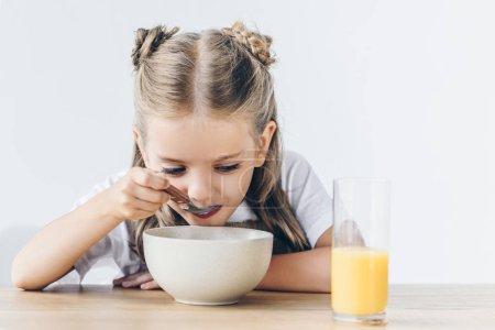 hungry little schoolgirl eating healthy breakfast isolated on white