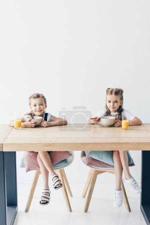 schoolgirls eating cereals for breakfast together on white