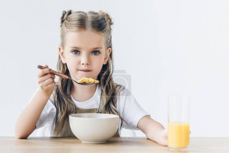 little schoolgirl eating healthy breakfast isolated on white and looking at camera