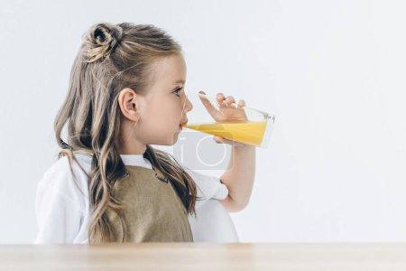 cute little schoolgirl with drinking orange juice isolated on white