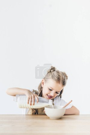 smiling little schoolgirl pouring milk into cereal for breakfast isolated on white