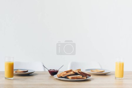 plate with toasts on table with bowl of jam and orange juice for breakfast