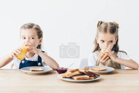 schöne kleine Schwestern, die Toasts mit Marmelade essen und Orangensaft zum Frühstück trinken, isoliert auf weiß
