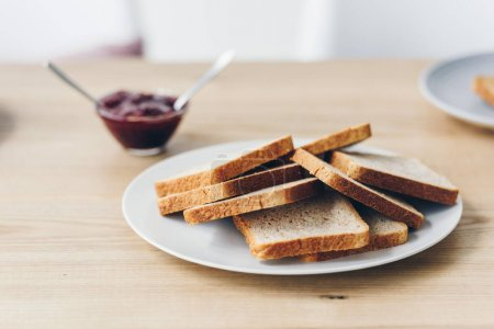 close-up shot of plate with toasts on table with bowl of jam for breakfast