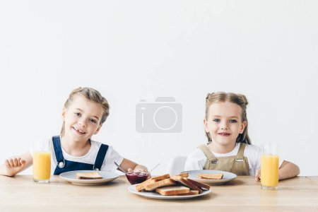 little sisters eating toasts with jam for breakfast and looking at camera isolated on white