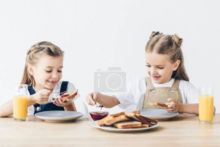 smiling little sisters eating applying jam onto toasts for breakfast isolated on white