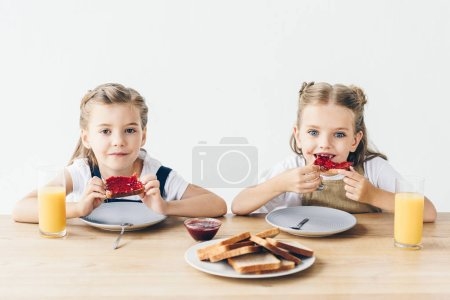 little sisters eating toasts with jam for breakfast isolated on white