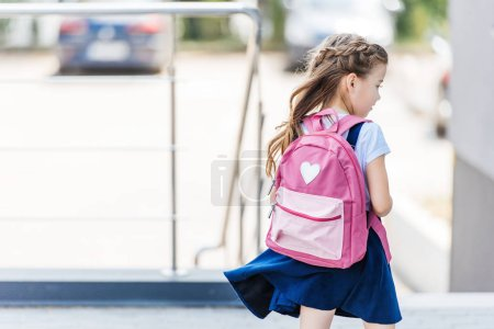 rear view of little schoolgirl with backpack on street