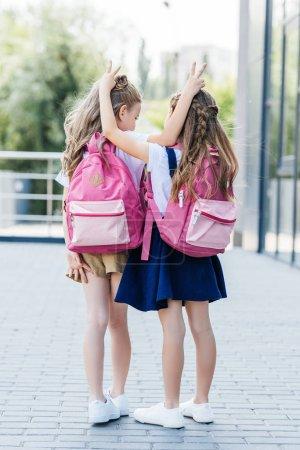 Photo pour Vue arrière de petites écolières faisant cornes blague geste les uns aux autres sur la rue - image libre de droit