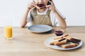 cropped shot of little child eating toast with jam isolated on white