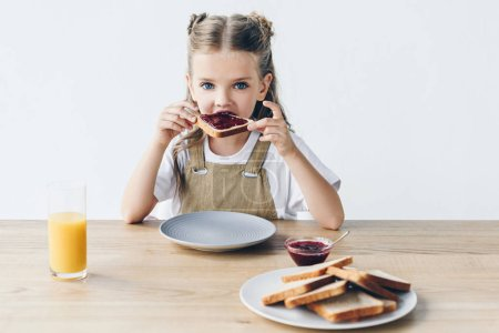 Photo for Adorable little schoolgirl eating toast with jam isolated on white - Royalty Free Image