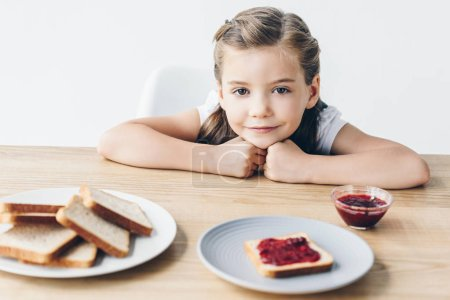 adorable little schoolgirl with toasts and jam for breakfast looking at camera isolated on white