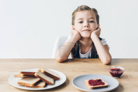 thoughtful little schoolgirl with toasts and jam for breakfast looking at camera isolated on white