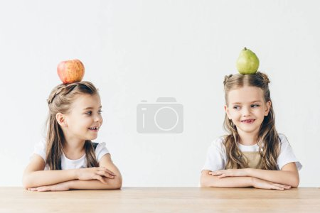 happy little schoolgirls with apple and pear on heads sitting at table isolated on white