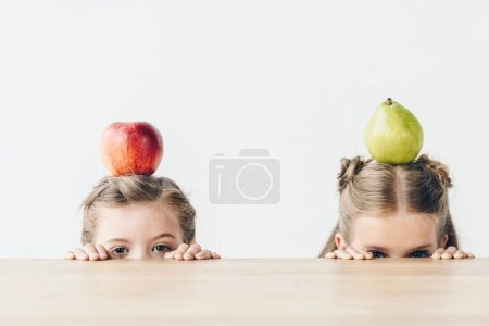 Photo for Little schoolgirls with apple and pear on heads hiding behind table isolated on white - Royalty Free Image