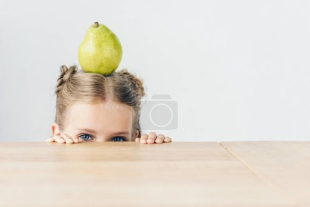 little schoolgirl with ripe pear on head peeping from behind tabletop isolated on white