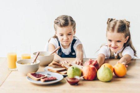 Foto de Hermanas pequeñas no quieren comer un desayuno saludable aislado en blanco - Imagen libre de derechos
