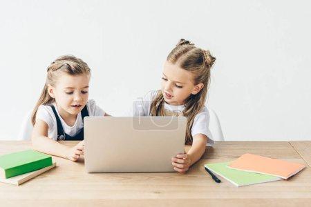 Photo pour Adorables petites écolières utilisant un ordinateur portable pour étudier isolé sur blanc - image libre de droit