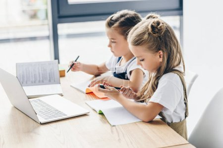 little schoolgirls using laptop and notebooks for studying isolated on white