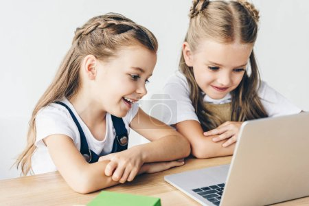 smiling little schoolgirls using laptop for studying isolated on white