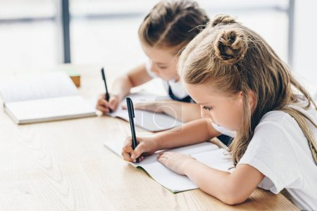 little schoolgirls writing in notebooks while doing homework isolated on white