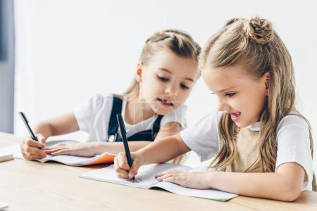 little schoolgirl cheating and copying work of her classmate isolated on white