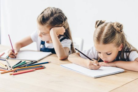 Photo for Focused little schoolgirls drawing with colorful pencils in albums together isolated on white - Royalty Free Image