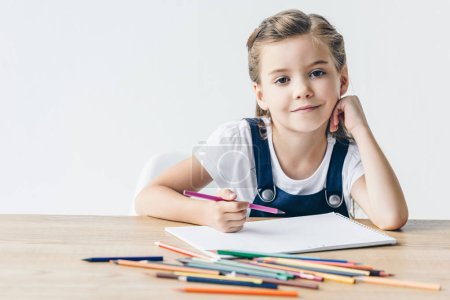 happy little schoolgirl drawing with color pencils and looking at camera isolated on white