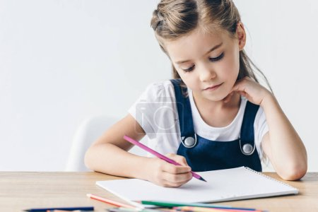 concentrated little schoolgirl drawing with color pencils isolated on white