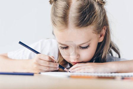 close-up shot of focused little schoolgirl drawing with color pencils isolated on white