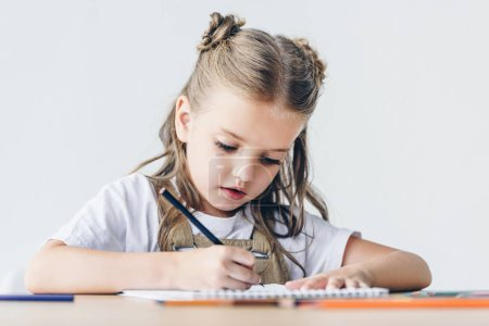little schoolgirl drawing with color pencils isolated on white