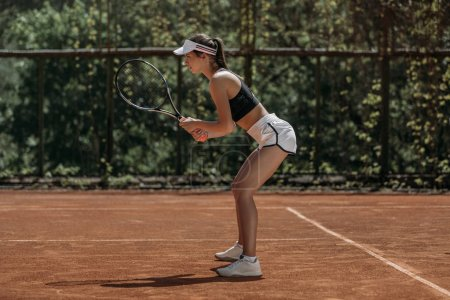 Photo for Young woman standing on tennis court waiting for serve - Royalty Free Image