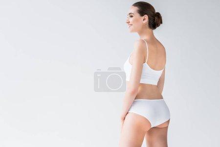 Photo pour Vue latérale de souriante jolie femme caucasienne en lingerie blanche isolée sur fond gris - image libre de droit