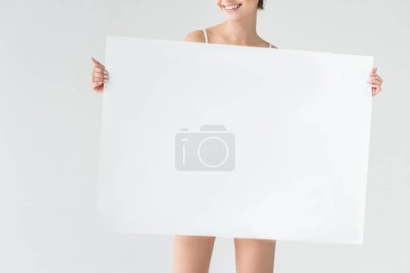 cropped image of smiling woman holding blank banner isolated on gray background