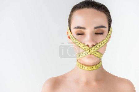 attractive young woman with closed mouth by measurement tape isolated on gray background