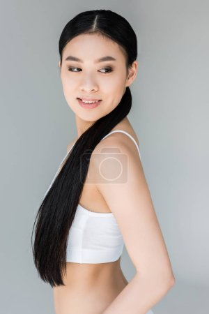 Photo for Smiling attractive asian young woman looking away isolated on gray background - Royalty Free Image