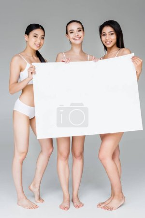 smiling multicultural women in lingerie holding blank banner isolated on gray background