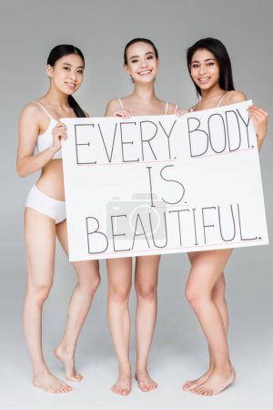 smiling multicultural women holding banner with lettering every body is beautiful isolated on gray background