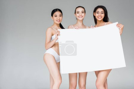 three smiling multicultural women in lingerie holding blank banner isolated on gray background