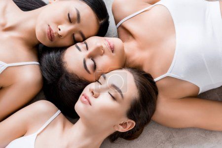 top view of beautiful tender multicultural girls with closed eyes